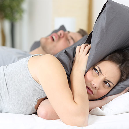 woman holding a pillow over her ears because of her husband's loud snoring